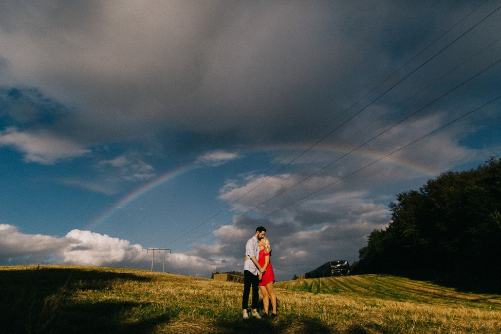 Wedding lovers hug underneath a beautiful rainbow, as documented by travel photographers.