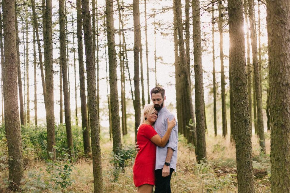 A lovely engagement portrait among tall trees in rural Aarhus, Denmark.
