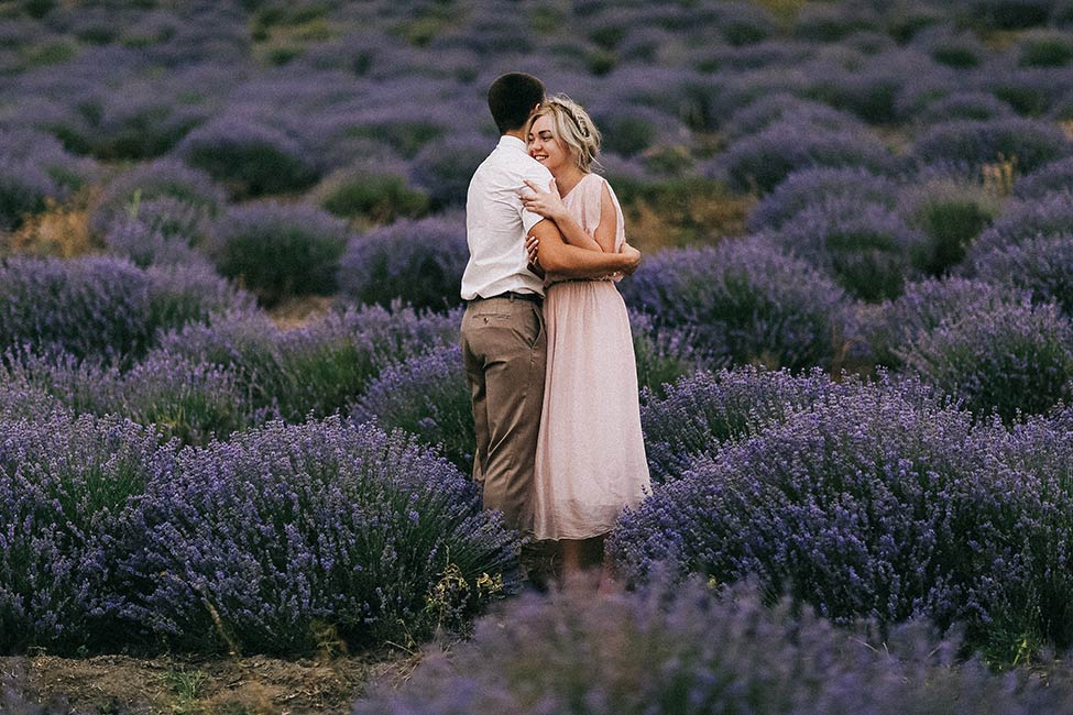 A couple hugs during their engagement photos in a lavender field.