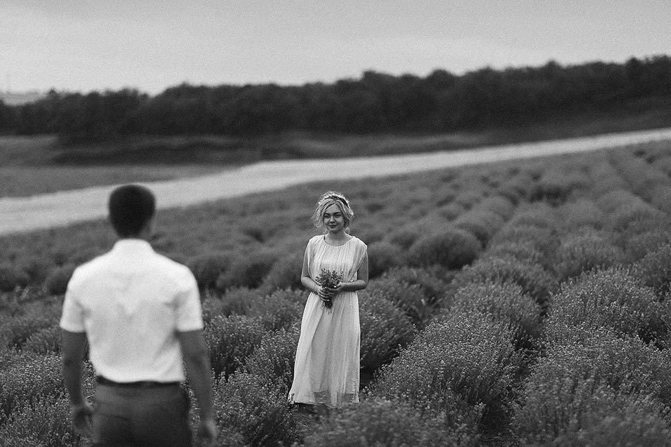A bride waiting for her groom in a field with a lavender bouquet in the south of France.