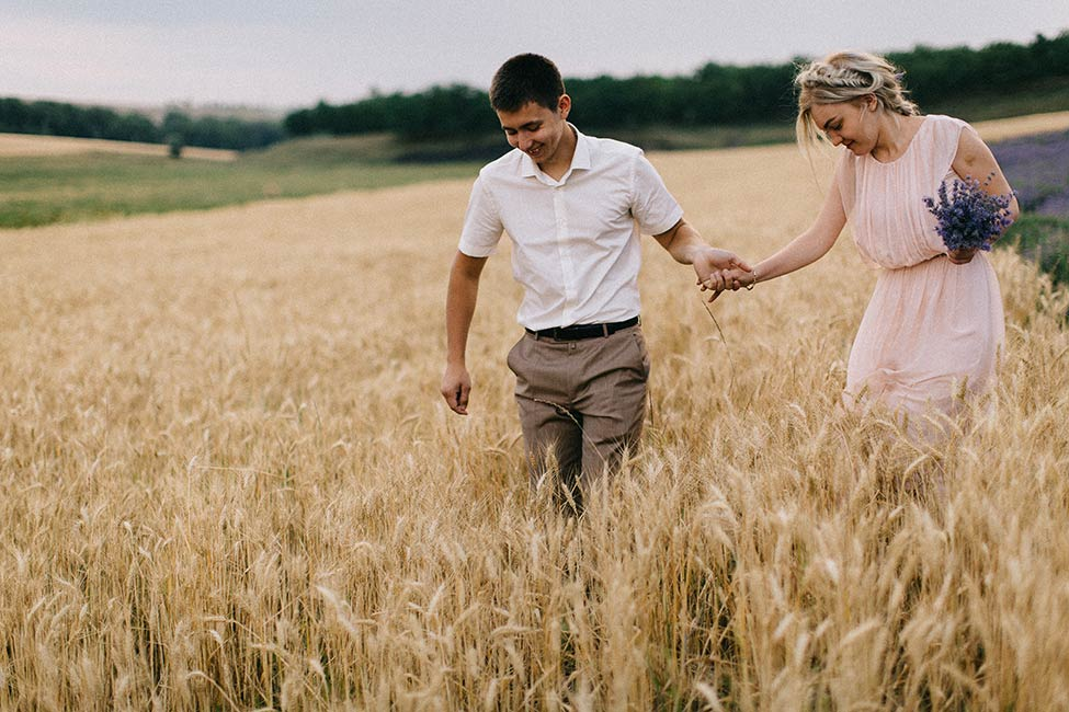 A couple walks through fields of wheat in Cobusca Noua, MD on their wedding day adventure.