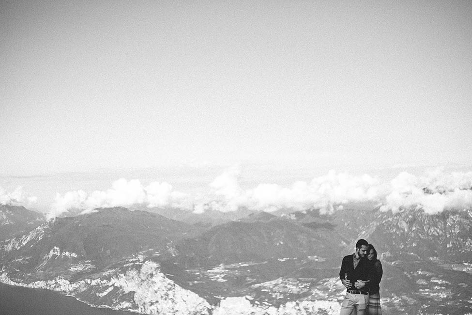Enrico and Eleonora embrace above the clouds, during their engagement session on monte baldo.